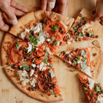 Animated image of hands grabbing pizza slices featuring Beyond Meat Crumbles