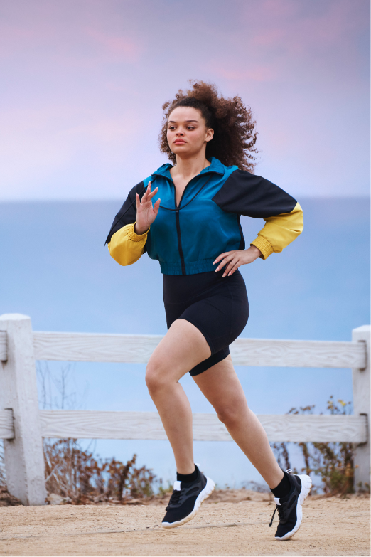 Active woman jogging on a trail overlooking the ocean